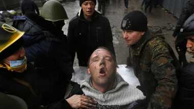 An injured man struggles to breathe as he is carried on a stretcher by anti-government protesters after clashes with riot police in the Independence Square in Kiev