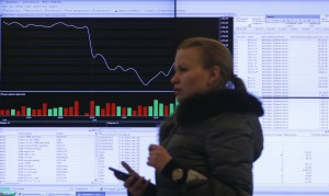 A woman walks past an information screen on display inside the office of the Moscow Exchange in the capital Moscow