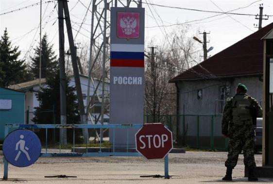 A Ukrainian border guard stands at a Russian-Ukrainian border crossing near the village of Uspenka